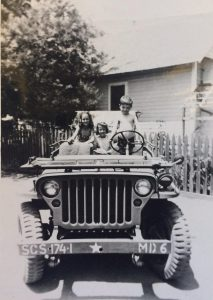 David Mason, about 4 years old, behind the wheel of the military jeep that was parked in front of his Fox Street home. Janice Cornine (middle) and Joyce Nichols (left) are not afraid of David's driving skills! Servicemen's wives lived with David's family, so servicemen would come in the jeep from the Ojai Valley Inn to visit their wives at David's home.