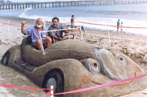 Dennis Shives and MAD Magazine cartoonist Sergio Aragones in a sand sculpture car by Shives.